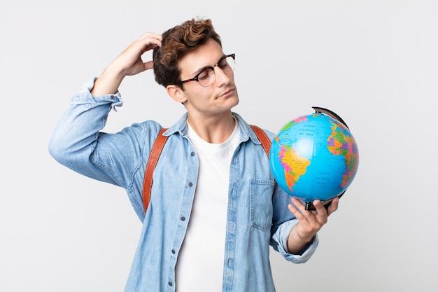 Jonge knappe man die zich verbaasd en verward voelt, hoofd krabben. student met een wereldbolkaart