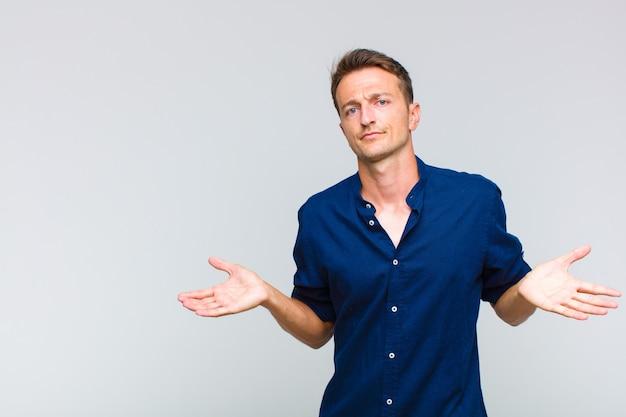 Jonge knappe man die zich verbaasd en verward voelt, onzeker is over het juiste antwoord of de juiste beslissing, probeert een keuze te maken