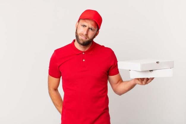 Jonge knappe man die zich verbaasd en verward voelt. pizza bezorgconcept
