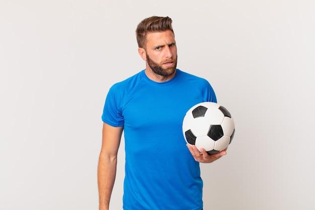 Jonge knappe man die zich verbaasd en verward voelt. voetbal concept