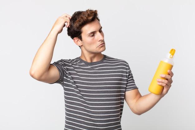 Jonge knappe man die zich verbaasd en verward voelt, zijn hoofd krabt en een koffiethermoskan vasthoudt