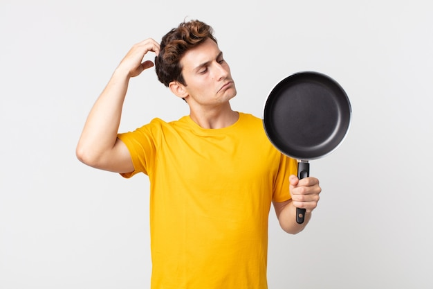 Jonge knappe man die zich verbaasd en verward voelt, zijn hoofd krabt en een kookpan vasthoudt