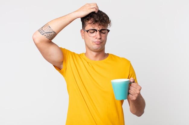 Jonge knappe man die zich verbaasd en verward voelt, zijn hoofd krabt en een kopje koffie vasthoudt