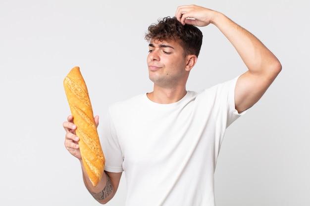 Jonge knappe man die zich verbaasd en verward voelt, zijn hoofd krabt en een stokbrood vasthoudt