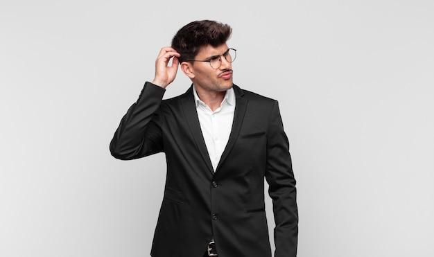 Jonge knappe man die zich verbaasd en verward voelt, zijn hoofd krabt en naar de zijkant kijkt