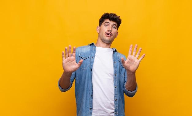 Jonge knappe man die zich verdoofd en bang voelt, bang is voor iets angstaanjagends, met de handen vooraan open en zegt: blijf weg