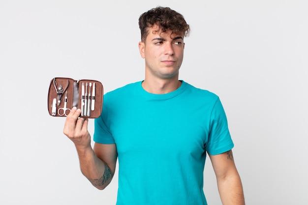 Jonge knappe man die zich verdrietig, overstuur of boos voelt en naar de zijkant kijkt en een spijkergereedschapkoffer vasthoudt