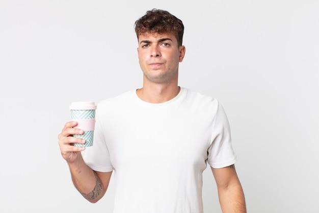 Jonge knappe man die zich verdrietig, overstuur of boos voelt en opzij kijkt en een afhaalkoffie vasthoudt