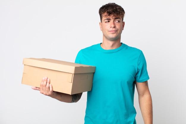 Jonge knappe man die zich verdrietig, overstuur of boos voelt en opzij kijkt en een kartonnen doos vasthoudt
