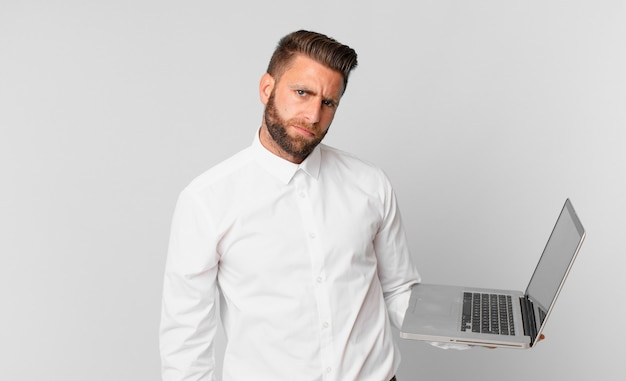 Jonge knappe man die zich verdrietig, overstuur of boos voelt en opzij kijkt en een laptop vasthoudt