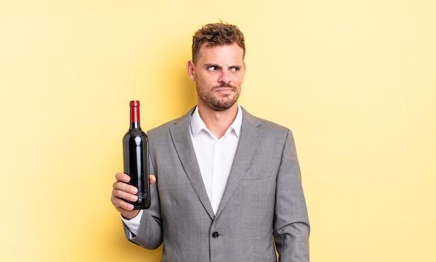 Jonge knappe man die zich verdrietig, overstuur of boos voelt en opzij kijkt. fles wijn concept