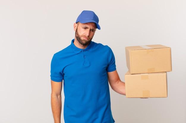 Jonge knappe man die zich verdrietig, overstuur of boos voelt en opzij kijkt. pakket leveren concept