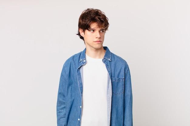 Jonge knappe man die zich verdrietig, overstuur of boos voelt en opzij kijkt
