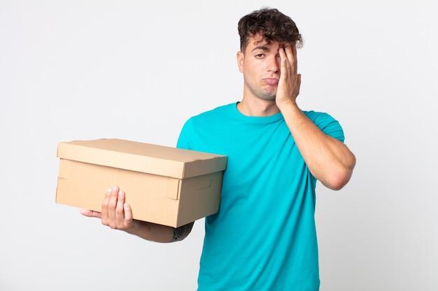 Jonge knappe man die zich verveeld, gefrustreerd en slaperig voelt na een vermoeiende bezigheid en een kartonnen doos vasthoudt