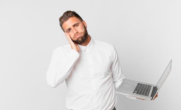 Jonge knappe man die zich verveeld, gefrustreerd en slaperig voelt na een vermoeiende bezigheid en een laptop vasthoudt