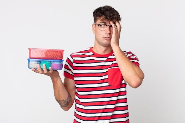 Jonge knappe man die zich verveeld, gefrustreerd en slaperig voelt na een vermoeiende lunch en een lunchpakket vasthoudt