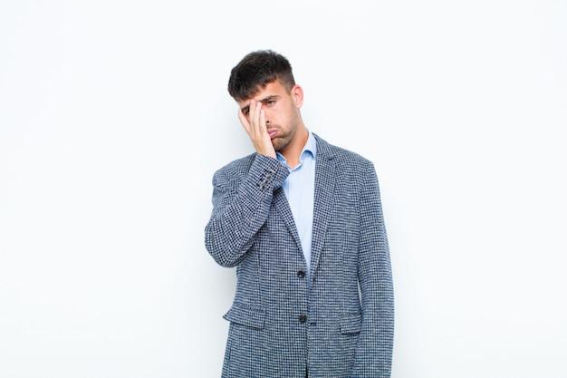 Jonge knappe man die zich verveeld, gefrustreerd en slaperig voelt na een vermoeiende, saaie en vervelende taak, gezicht met hand vasthoudend tegen witte muur