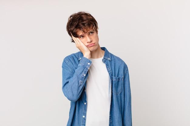 Jonge knappe man die zich verveeld, gefrustreerd en slaperig voelt na een vermoeiende