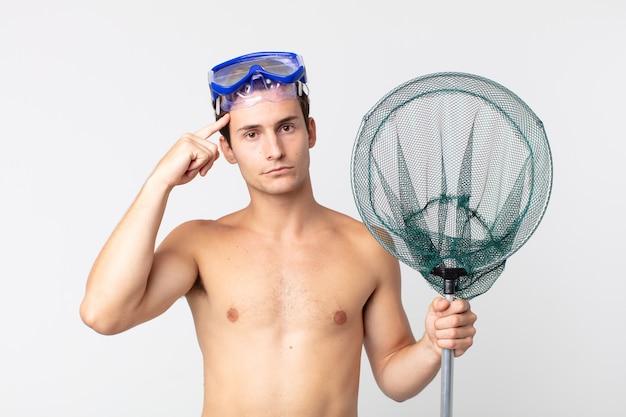 Jonge knappe man die zich verward en verbaasd voelt en laat zien dat je gek bent met een bril en een visnet