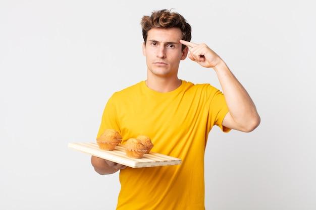 Jonge knappe man die zich verward en verbaasd voelt en laat zien dat je gek bent met een dienblad met muffins