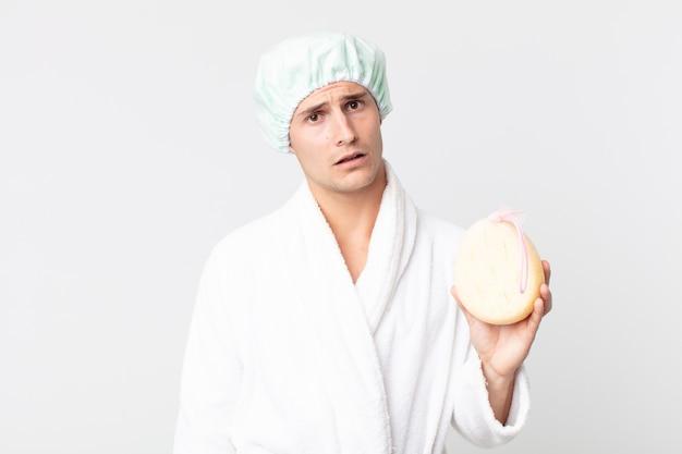 Jonge knappe man die zich verward en verward voelt met badjas, douchemuts en een spons