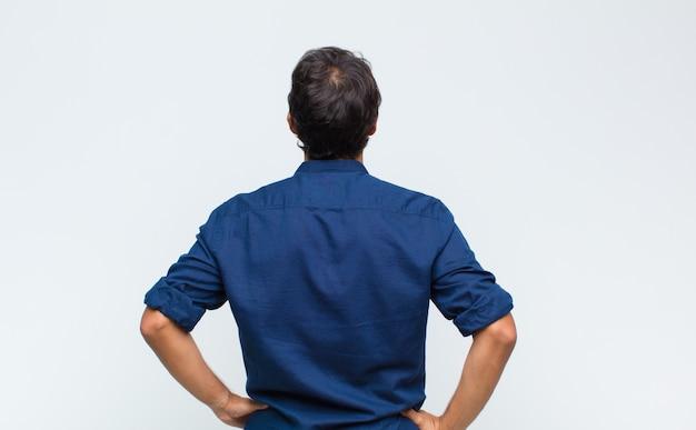 Jonge knappe man die zich verward of vol voelt of twijfels en vragen, zich afvraagt, met de handen op de heupen, zicht naar achteren