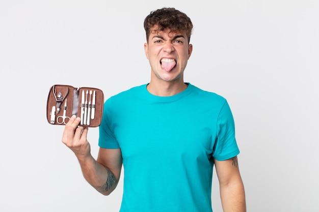 Jonge knappe man die zich walgt en geïrriteerd voelt en zijn tong uitsteekt en een spijkergereedschapkoffer vasthoudt