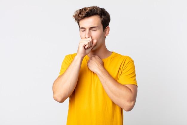 Jonge knappe man die zich ziek voelt met een zere keel en griepsymptomen, hoesten met bedekte mond