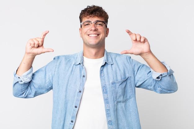 Jonge knappe man die zijn eigen glimlach met beide handen inkadert of schetst, er positief en gelukkig uitziet, wellnessconcept