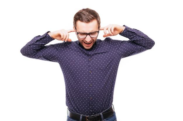 Jonge knappe man die zijn oren bedekt en ruis op de witte muur negeert