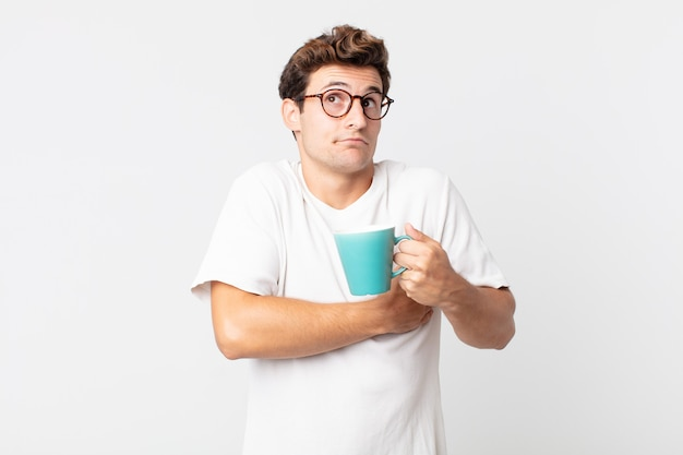 Jonge knappe man die zijn schouders ophaalt, zich verward en onzeker voelt en een koffiekopje vasthoudt