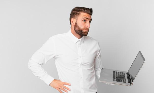 Jonge knappe man die zijn schouders ophaalt, zich verward en onzeker voelt en een laptop vasthoudt