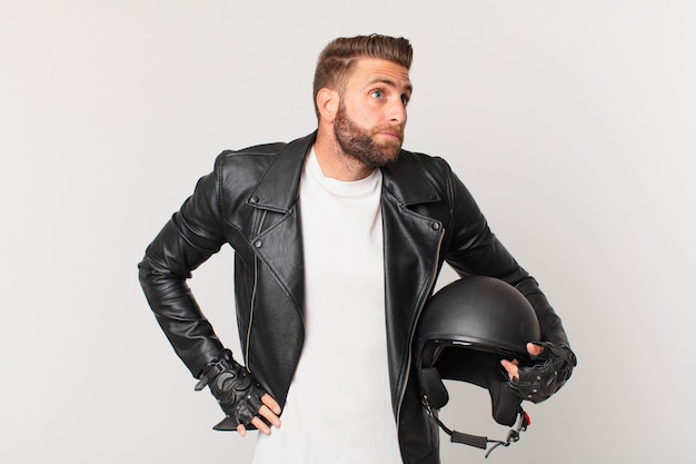 Jonge knappe man die zijn schouders ophaalt, zich verward en onzeker voelt. motorhelm concept