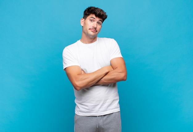 Jonge knappe man die zijn schouders ophaalt, zich verward en onzeker voelt, twijfelt met gekruiste armen en een verbaasde blik