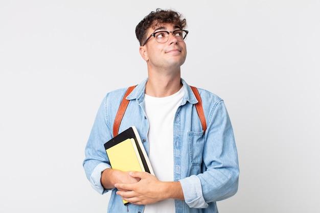 Jonge knappe man die zijn schouders ophaalt, zich verward en onzeker voelt. universitair studentenconcept