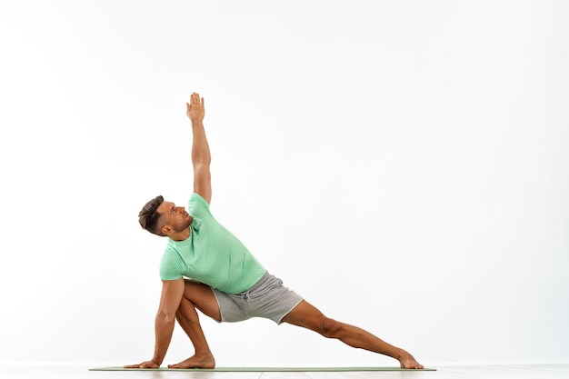 Jonge knappe man doet yoga geïsoleerd op wit Premium Foto