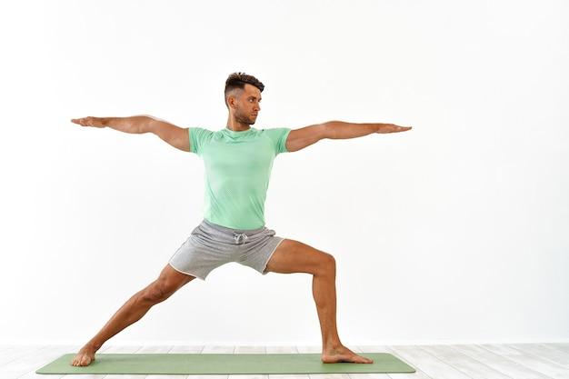 Jonge knappe man doet yoga geïsoleerd op wit