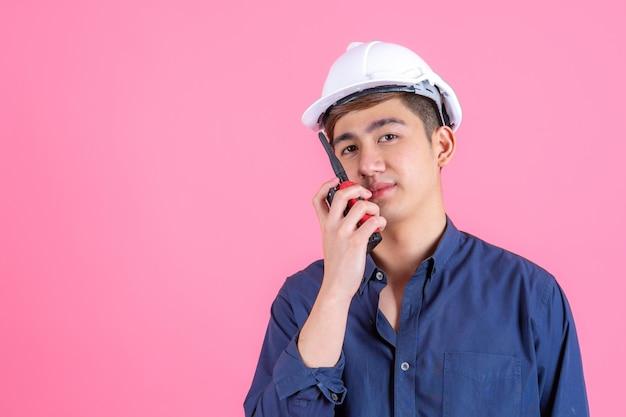 Jonge knappe man draagt witte helm en praten