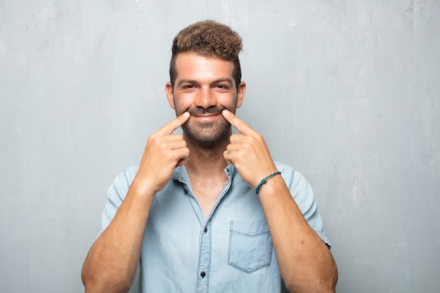 Jonge knappe man dwingt een glimlach op gezicht met beide wijsvingers