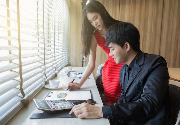 Jonge knappe man en jonge mooie vrouw die bedrijfs marketing grafiek bespreken op werkplaats