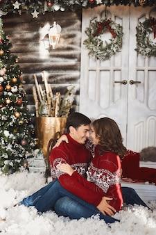 Jonge knappe man en mooie vrouw met lelijke truien die elkaar aankijken terwijl ze op de...