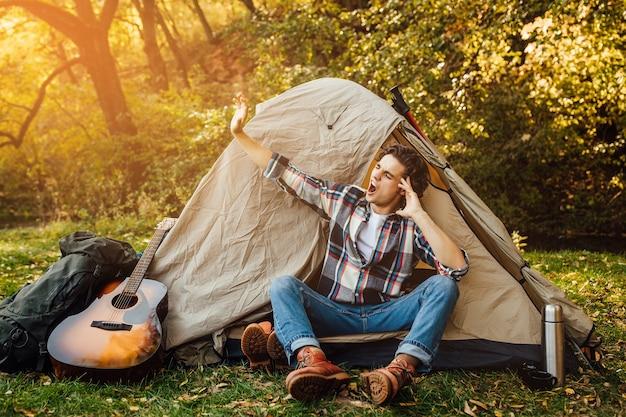 Jonge knappe man gaapt en strekt zich uit in de ochtend bij de tent op de camping in de natuur