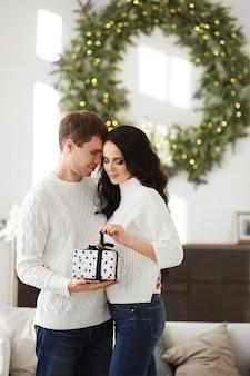 Jonge knappe man geeft een kerstcadeau aan zijn prachtige vriendin met lang donker haar