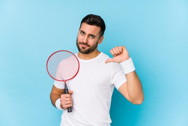Jonge knappe man geïsoleerd badminton voelt zich trots en zelfverzekerd, voorbeeld te volgen.