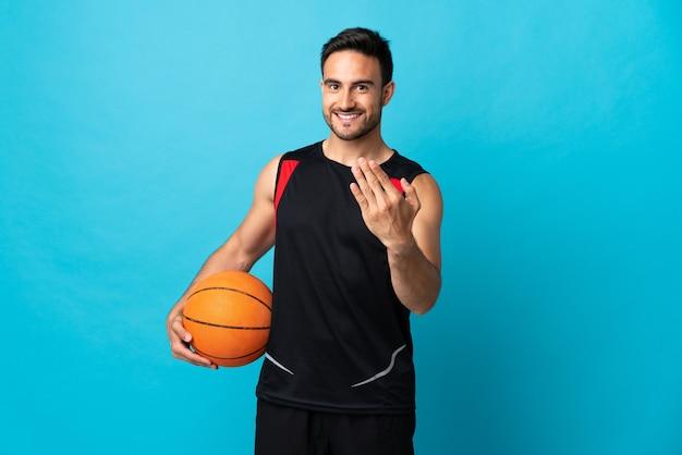 Jonge knappe man geïsoleerd op blauw basketbal spelen en komend gebaar doen
