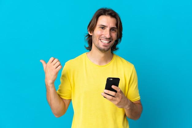Jonge knappe man geïsoleerd op blauw met behulp van mobiele telefoon en wijst naar de zijkant
