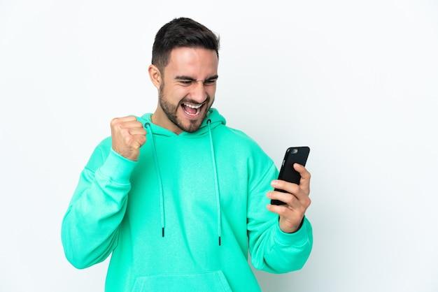 Jonge knappe man geïsoleerd op een witte muur met behulp van mobiele telefoon en overwinning gebaar doen