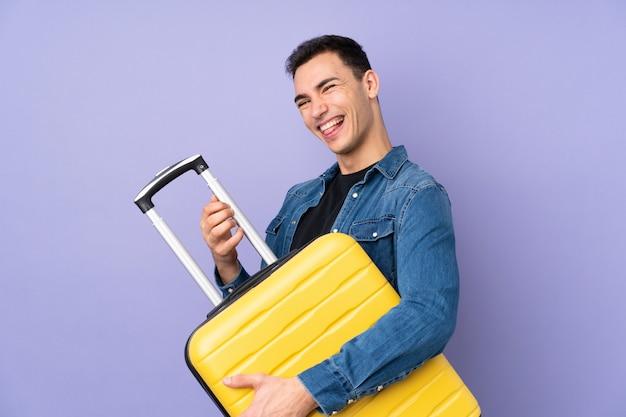 Jonge knappe man geïsoleerd op paarse muur in vakantie met een reiskoffer zoals een gitaar