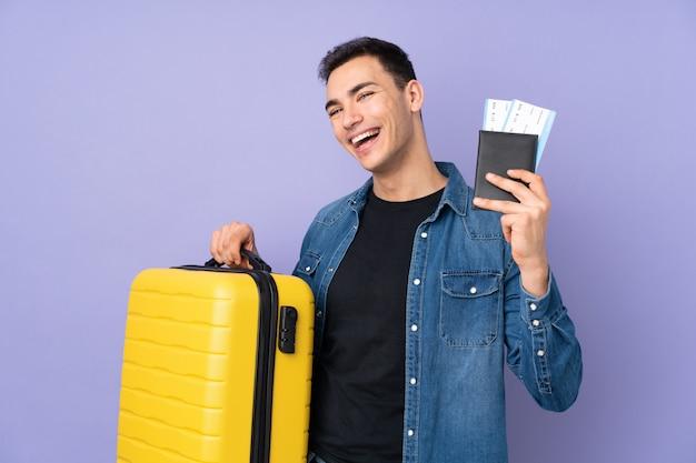 Jonge knappe man geïsoleerd op paarse muur in vakantie met koffer en paspoort