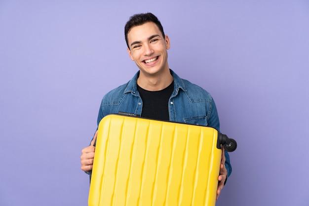 Jonge knappe man geïsoleerd op paarse muur in vakantie met reiskoffer